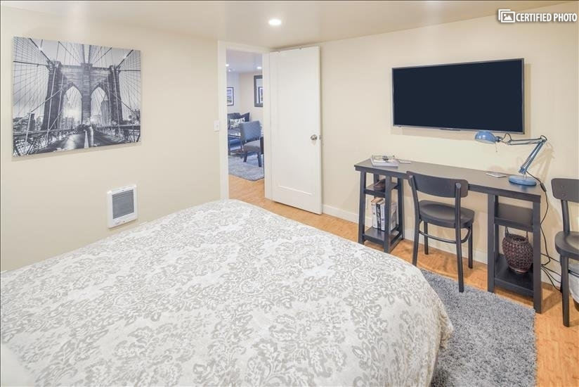Desk, TV, Queen sized bed, and artwork in the Larger bedroom