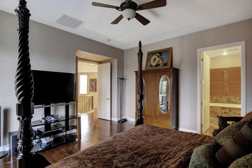 Master bedroom wood floor antique armoir & Kings chair