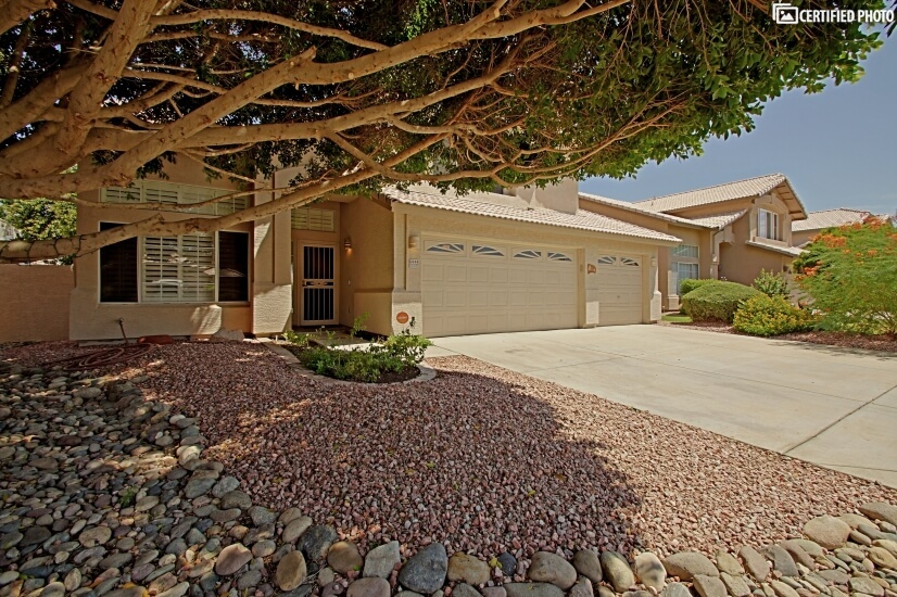 Impeccable landscaping of rock beds, flowering shrubs, and a