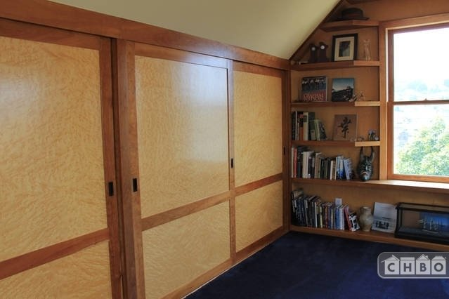 Sliding bird eye maple closet doors with dressers in the Mas