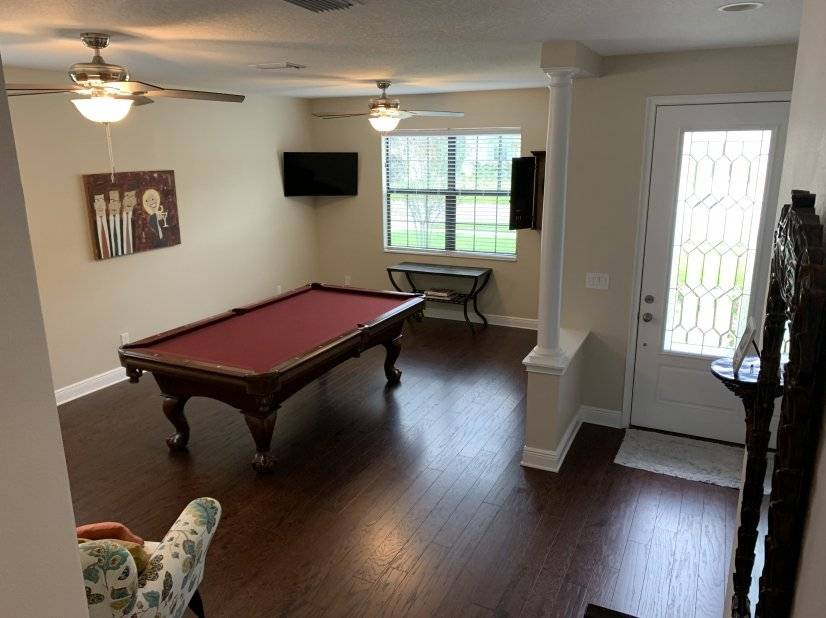 Game room with pool table, TV and Dart board.