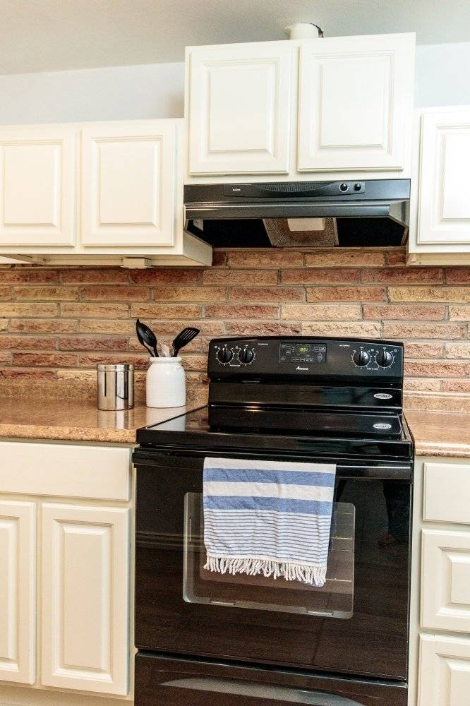 Fullsize electric stove with glass cooktop.