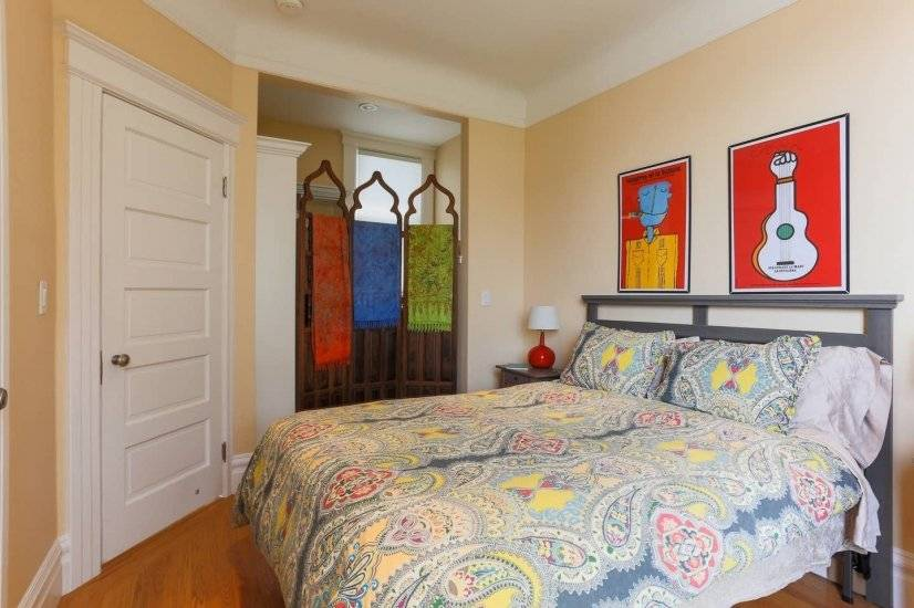 2nd bedroom has stained glass panels & cheerful original art