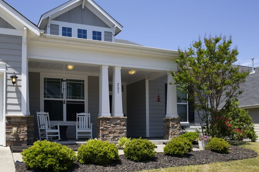 Landscaped front exterior with rocking chairs