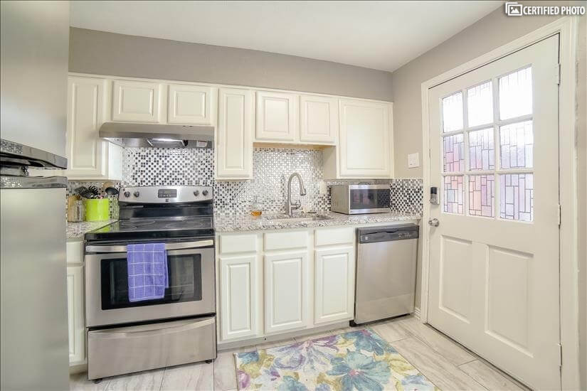 Modern white cabinets and stainless steel appliances.