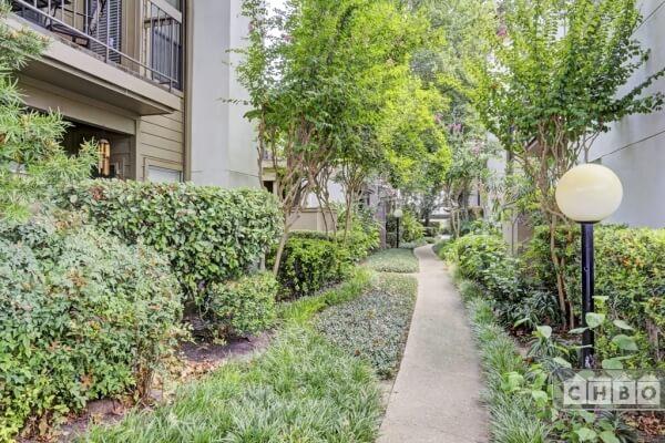 Lush landscaping on walkway.