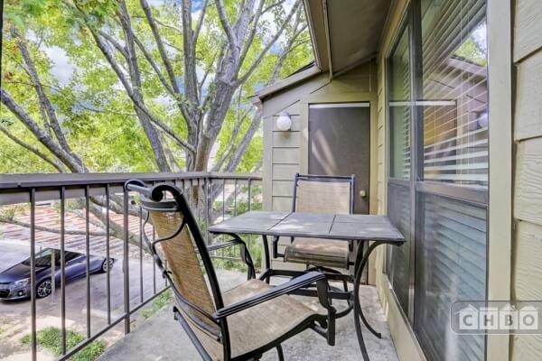 Patio set on the balcony overlooking beautiful courtyard.