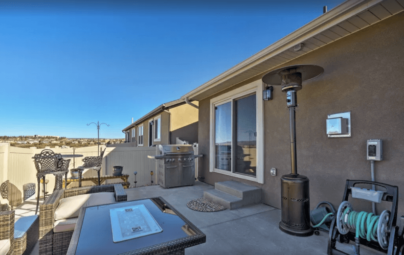 Spacious rear patio with furniture, fire pit