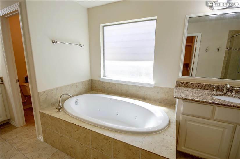 Large bathtub and separate bathroom area