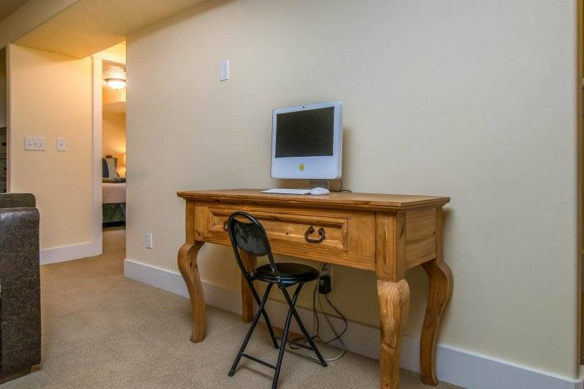 Desk with computer in basement family room