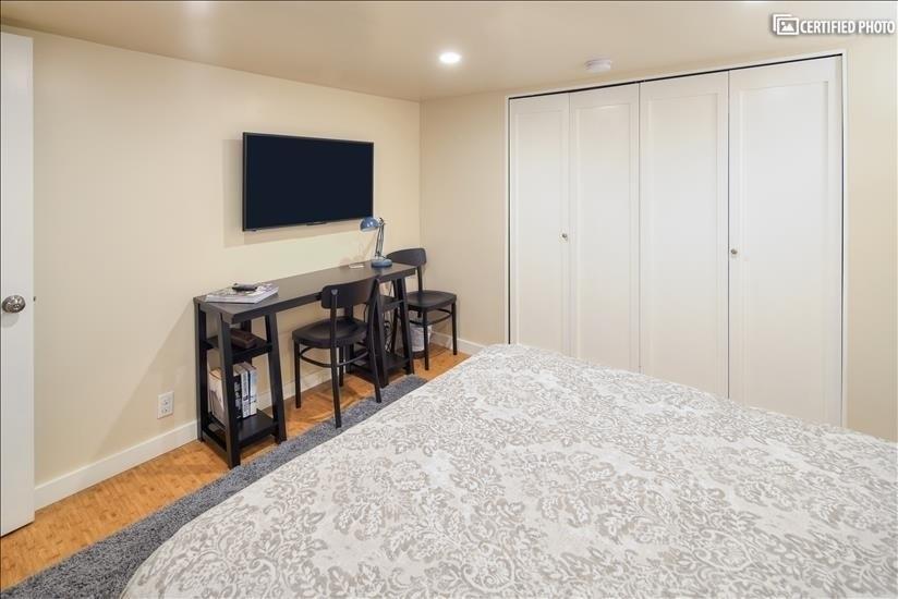 Desk and 40 inch 4K UHD Roku TV in larger bedroom