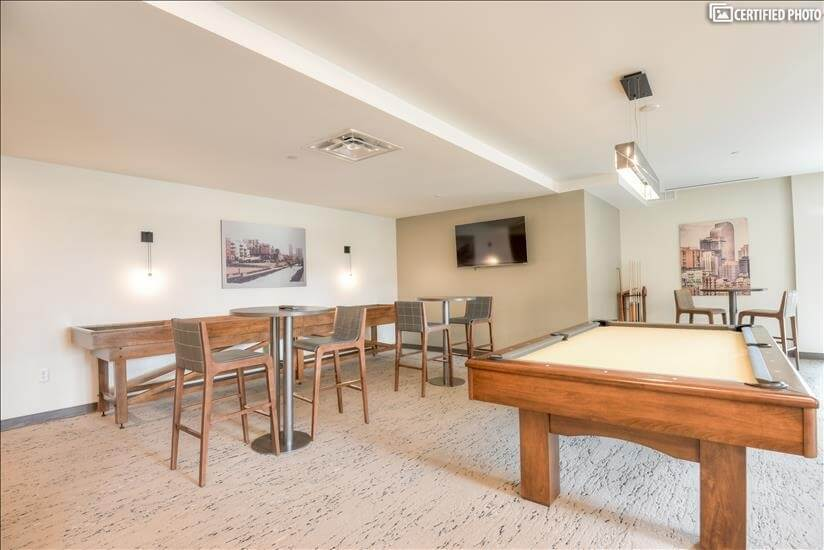 Community room with shuffleboard, pool table and a grand pia