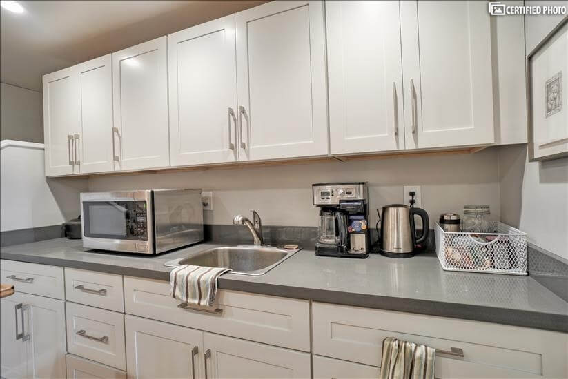 Kitchen cabinets, microwave, tea kettle, coffee maker