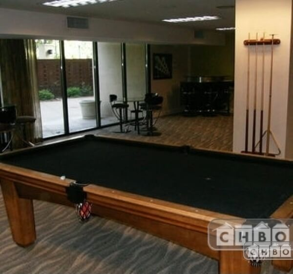 Billiards party room with bar and large flat screen televisi