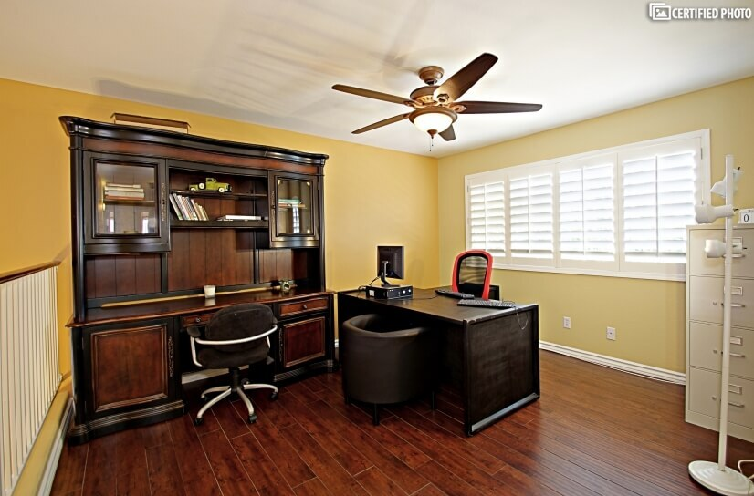 Full office with PC workstation and dark wood furniture.