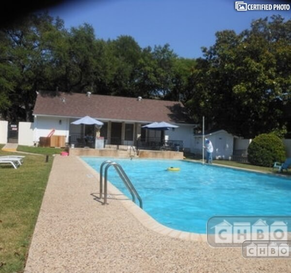 Large well kept swimming pool. Tables and cha