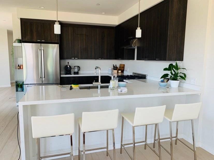 White leather stools at spacious waterfall kitchen peninsula