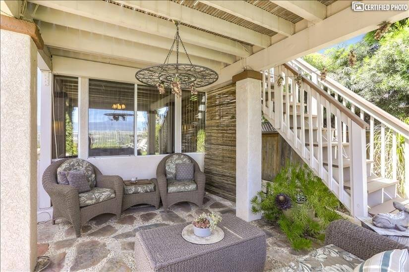 Seating area under the deck with two chairs and sofa.