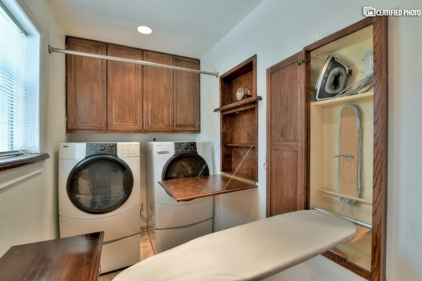 Laundry room with ironing board and folding area.