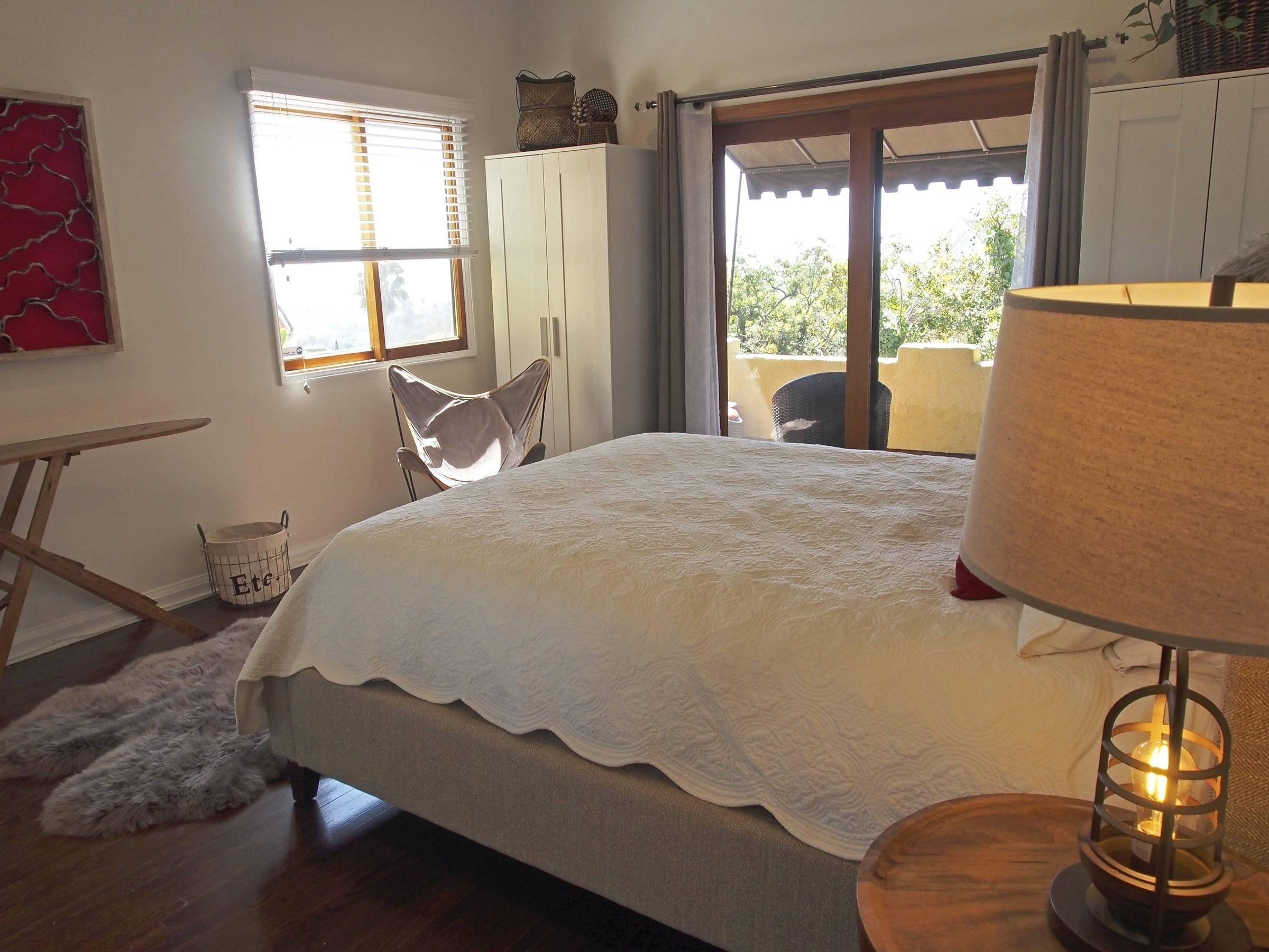 bedroom with window and sliding door to deck.