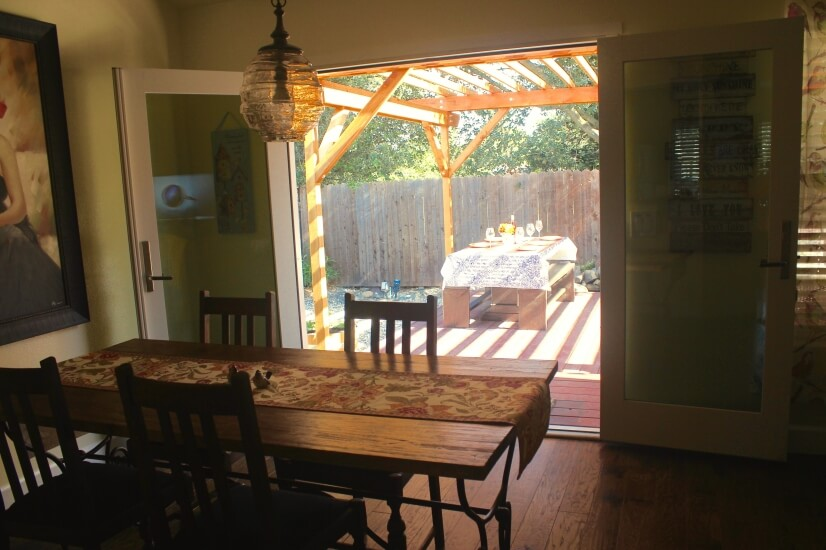 Doors open to covered deck with water feature