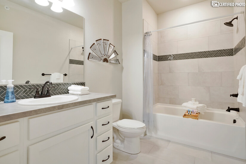 Secondary bath with tub/shower combo & modern tile accents