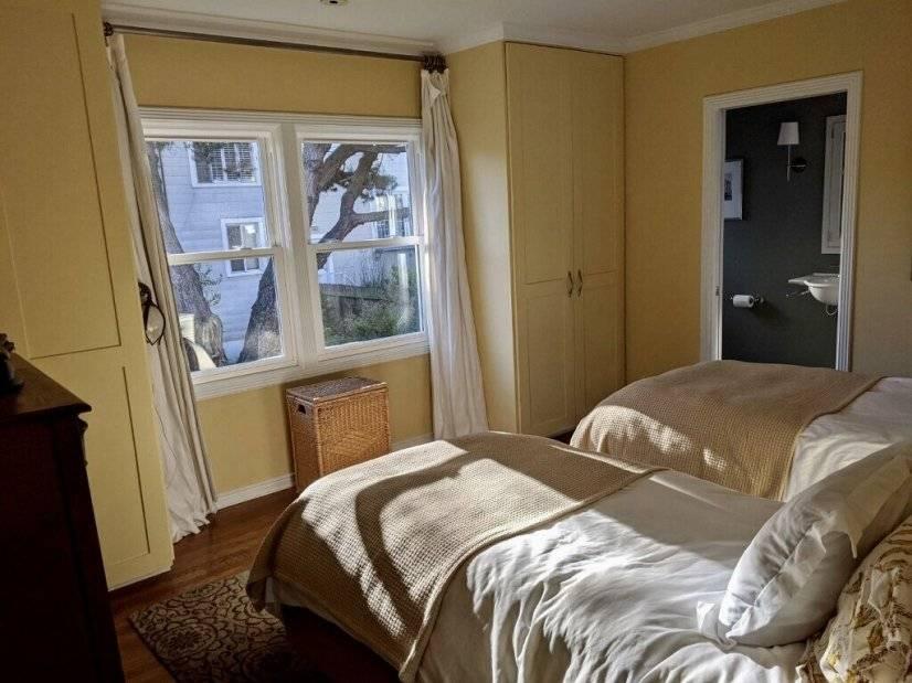 Guest bedroom has twin beds, full bath, garden views