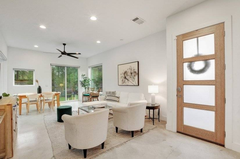 Dining, living, and entry with warm toned woo