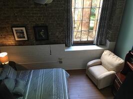 Bedroom with exposed brick, queen bed, huge windows